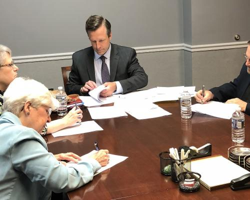 Carole Shinnick, SSND; Christine Beckett, SCN; and John Pavlik, OFM Cap with the lawyer signing paperwork for the sale of the office building